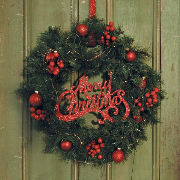 Christmas Wreath hanging on the green wooden door with Merry Christmas sign