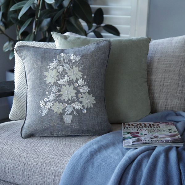 Silver tree cushion cover placed on the couch with 2 other cushions behind, home magazine also placed with the blanket