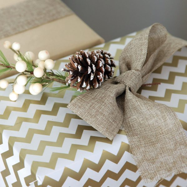 Best Secret Santa Gifts for your Workmates Wrapped Christmas Gift with a brown Bow and a pine cone zommed in