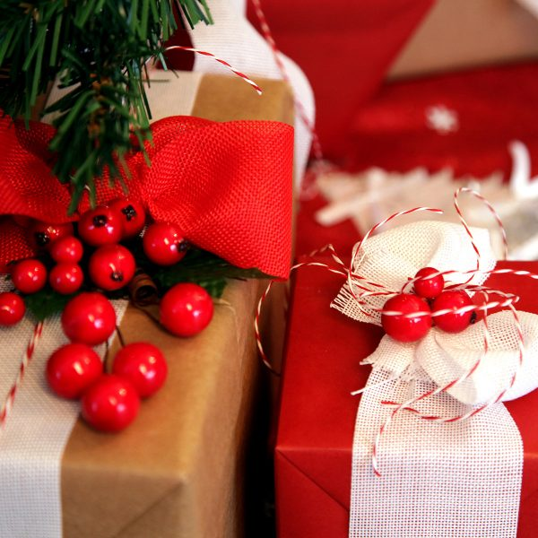 Best Secret Santa Gifts for your Workmates two wrapped Christmas Gifts with red bow and red berry pick