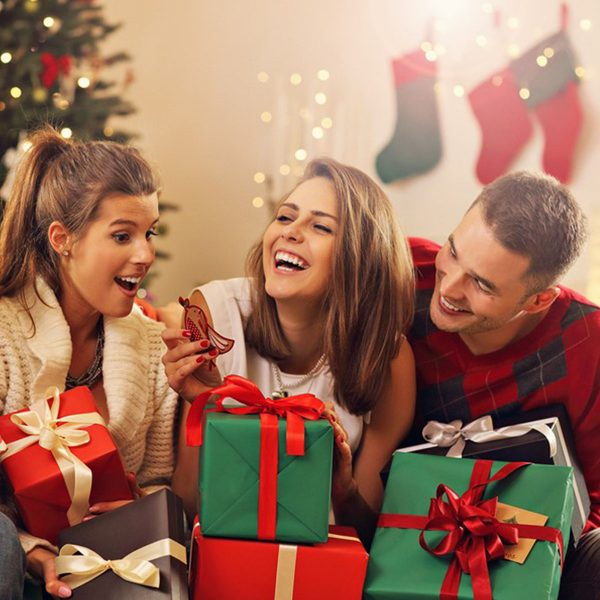 Three people sitting in the living room and looks excited while holding their presents the middle woman is holding something