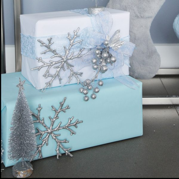 Gift boxed, wrapped in blue ribbon with Silver Glitter Berry Christmas Garland on top grey with grey pillow behind