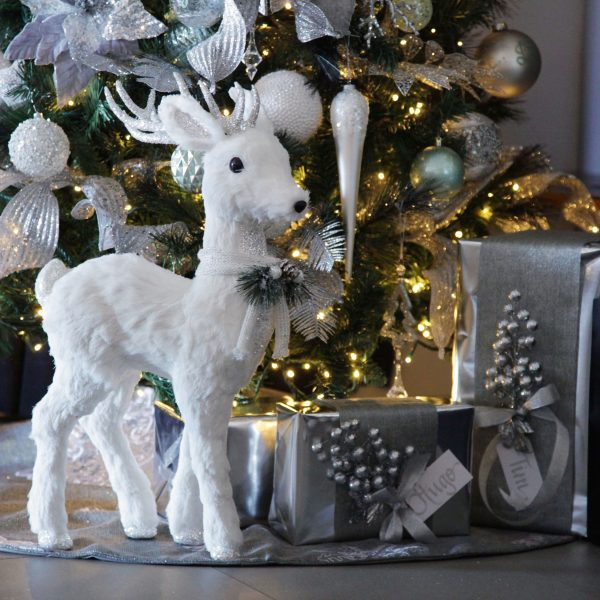 White Sisal Reindeer Stands behind the Big Christmas Tree and Silver wrapped presents with personalised gift tag