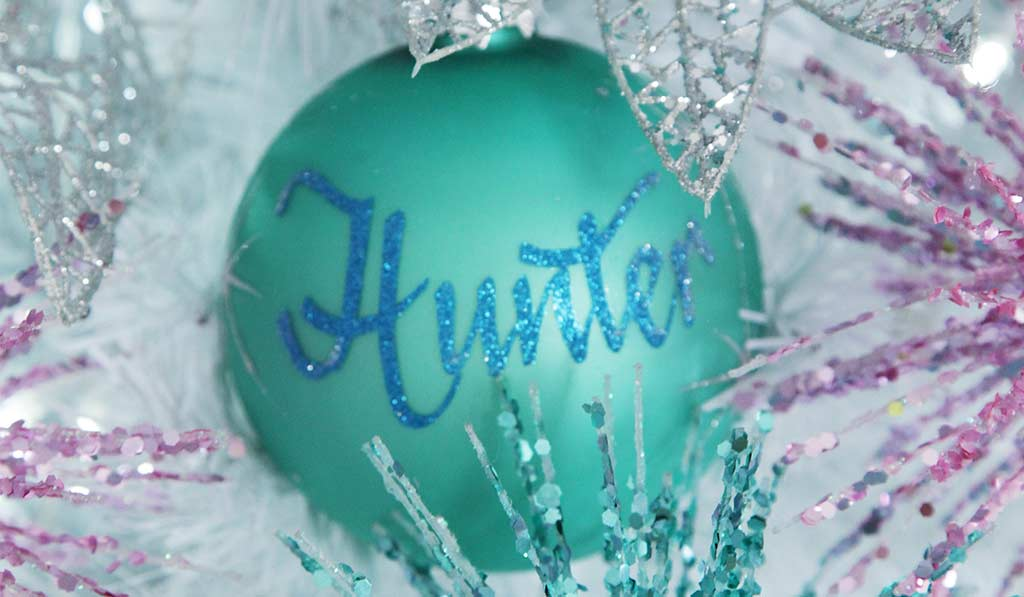 Sky blue Glass personalised Christmas bauble hanging on white Christmas tree name in blue glitter