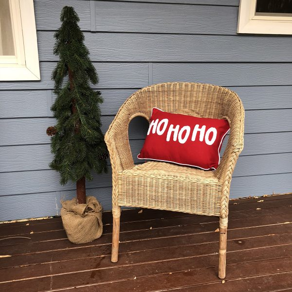 Ho Ho Ho Cushion placed in a wrattan chair outside with a small tree beside